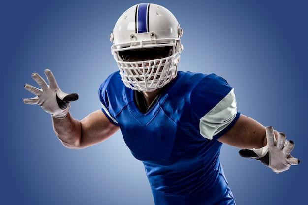 Fußballspieler mit einer blauen uniform, die einen angriff auf eine blaue wand macht