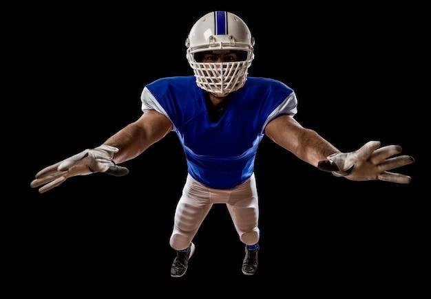 Fußballspieler mit einer blauen uniform, die einen angriff auf eine schwarze wand macht