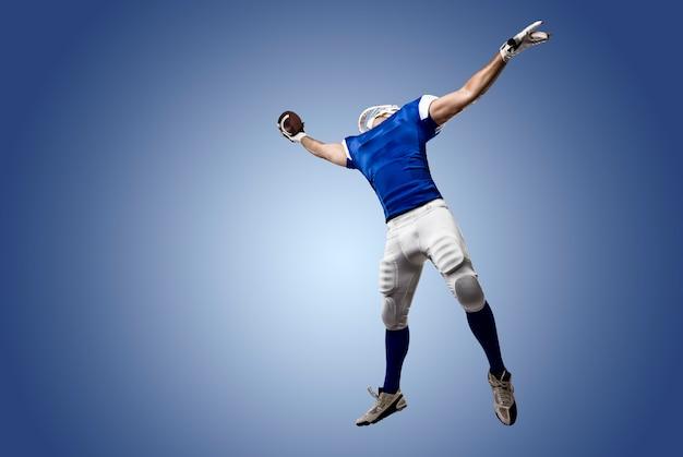 Fußballspieler mit einer blauen uniform, die einen haken an einer blauen wand macht