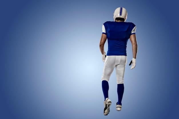 Fußballspieler mit einer blauen uniform, die seinen rücken auf einer blauen wand zeigt