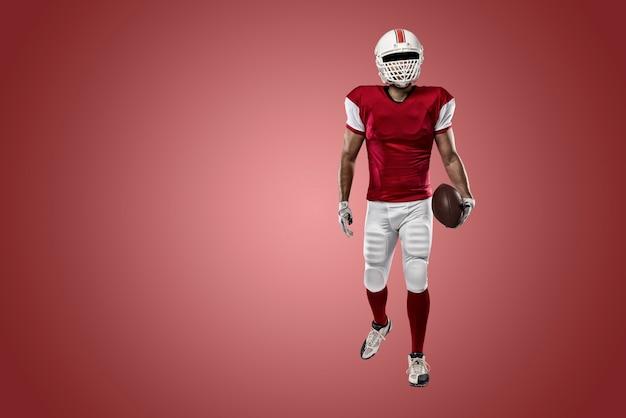 Fußballspieler mit einer roten uniform an einer roten wand