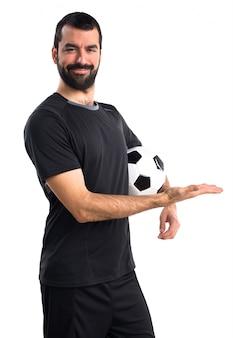 Fußballspieler präsentiert etwas