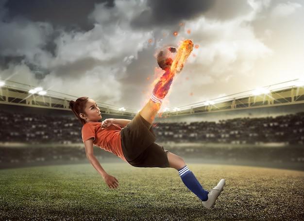 Fußballspieler treten feuerball auf dem stadion