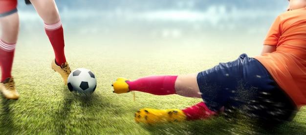 Fußballspielerfrau im orange trikot, das den ball von ihrem gegner schiebt
