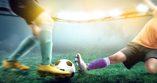 Fußballspielerfrau im orange trikot, das den ball von seinem gegner schiebt