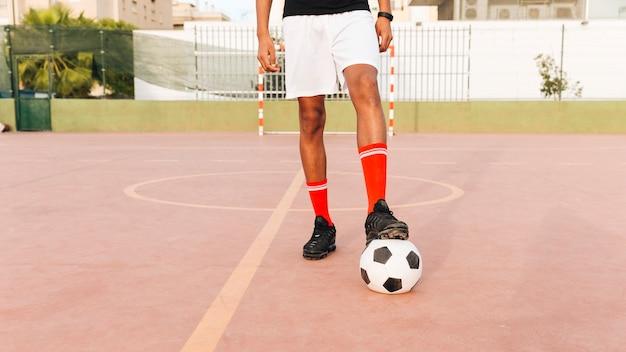 Fußballspielerfüße auf fußball am stadion am sonnigen tag