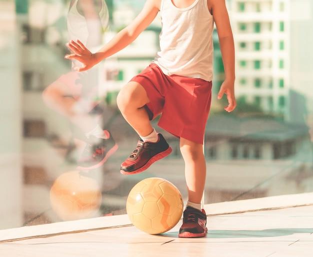 Fußballspielerjunge tritt auf den ball im raum