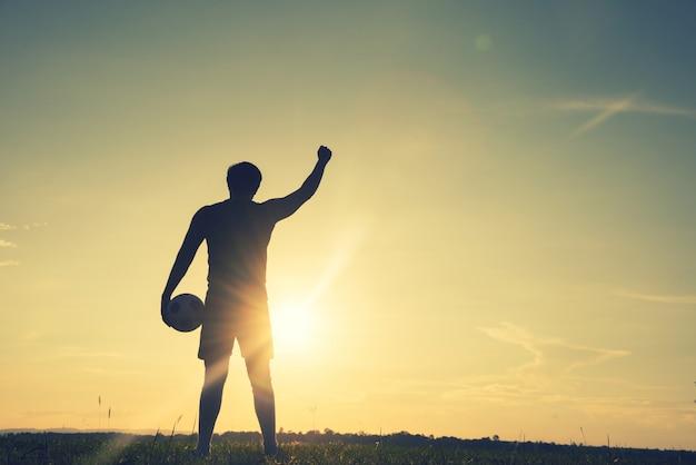 Fußballspielermann, der hintere ansicht im schattenbild lokalisiert auf sonnenunterganghintergrund steht