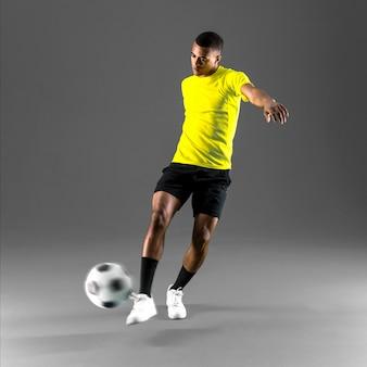 Fußballspielermann mit dunkelhäutigem spielen den ball auf dunklem hintergrund tretend