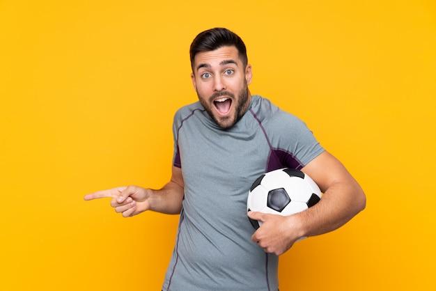Fußballspielermann über lokalisierter wand überrascht und seite zeigend