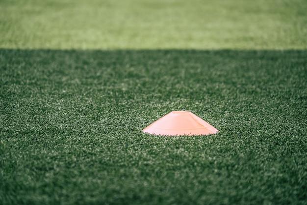Fußballsport-trainingsausrüstungs-markierungskegel auf grünem fußballtrainingsfeld im freien, für fußballsport-trainingskonzept.