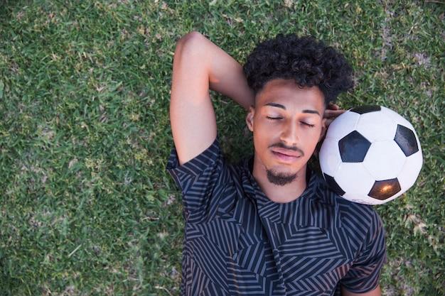 Fußballsportler, der pause auf fußballplatz hat