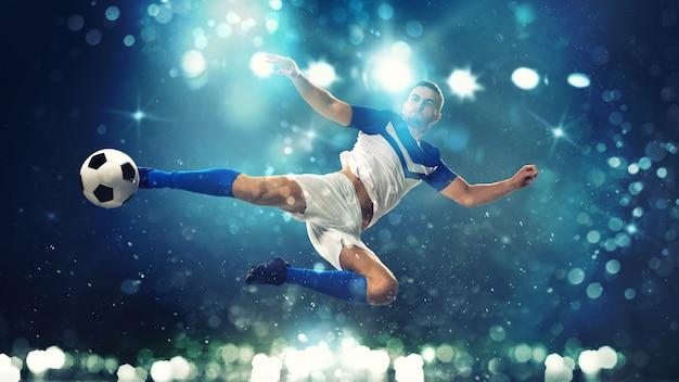 Fußballstürmer schlägt den ball mit einem akrobatischen tritt in die luft