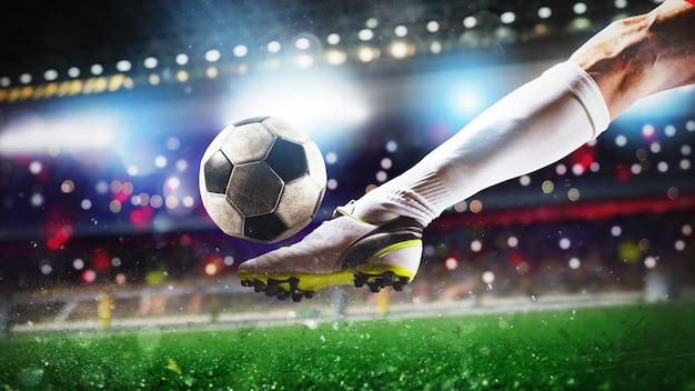 Fußballszene bei nachtspiel mit nahaufnahme eines fußballschuhs, der den ball mit kraft schlägt