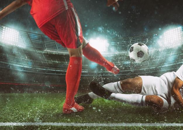 Fußballszene im stadion mit spieler in roter uniform, der den ball tritt, und gegner im zweikampf, um sich zu verteidigen