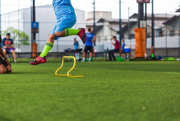 Fußballtaktiken auf rasen mit barriere zum trainieren der sprungfähigkeit von kindern in der fußballakademie