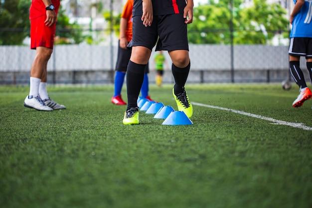 Fußballtaktiken auf rasen mit barrierekegel zum training der sprungfähigkeit von kindern in der fußballakademie