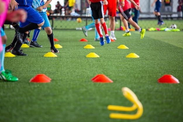 Fußballtaktiken auf rasen mit kegel für das training von thailand im hintergrund training von kindern in der fußballakademie