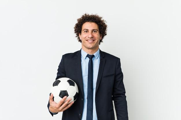 Fußballtrainer, der eine kugel glücklich, lächelnd und freundlich anhält.