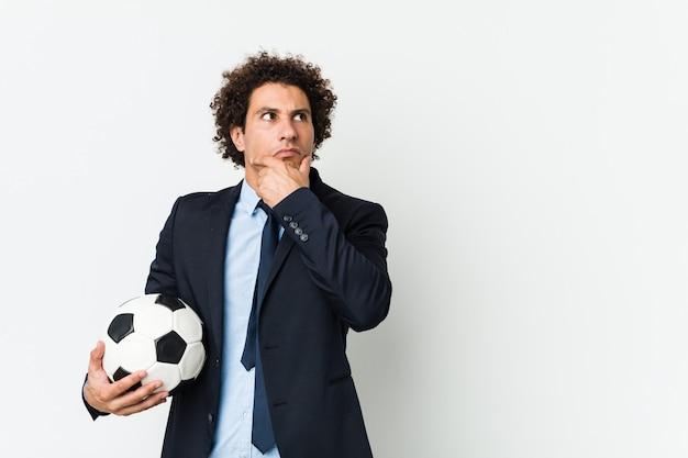 Fußballtrainer, der eine kugel seitlich schaut mit zweifelhaftem und skeptischem ausdruck anhält.