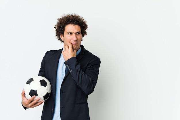 Fußballtrainer, der einen ball hält, entspannte sich und dachte an etwas, das einen kopierraum betrachtete.