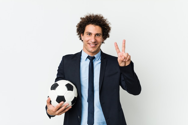 Fußballtrainer, der einen ball zeigt siegeszeichen und breit lächelt hält.