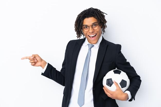 Fußballtrainer über lokalisierter weißer wand überrascht und finger auf die seite zeigend