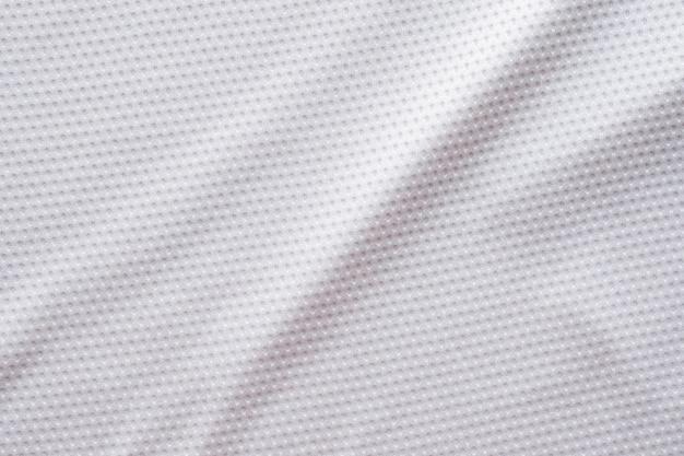 Fußballtrikot der weißen stoffsportkleidung mit hintergrund der luftmaschenstruktur