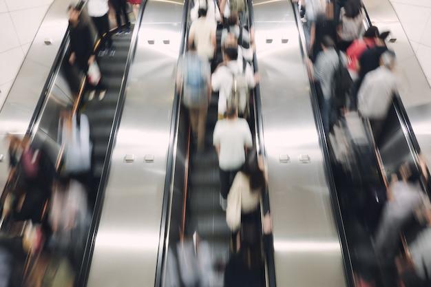 Fußgänger, angestellter auf und ab der automatischen rolltreppe