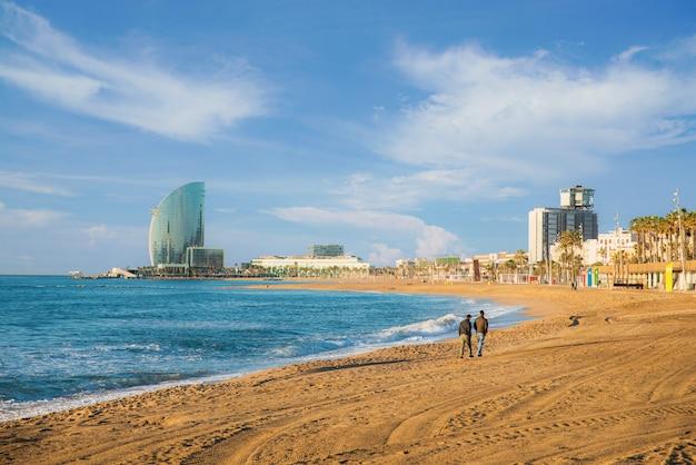 Fußgänger gehen entlang barceloneta-strand in barcelona mit buntem himmel bei sonnenaufgang. direkt am meer, strand, küste in spanien. vorort von barcelona, katalonien