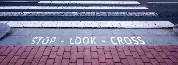 Fußgängerüberquerung. einsame straße mit fußgängertext: stopp, schauen, kreuzen. textur mit platz für text.