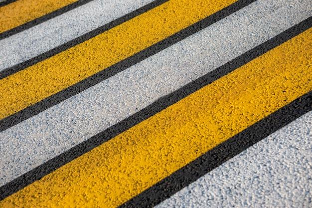 Fußgängerüberweg auf einer asphaltstraße in den strahlen der untergehenden sonne