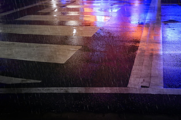 Fußgängerüberweg (zebraverkehrsweg) auf der nassen straße, regnerische nacht in der stadt.
