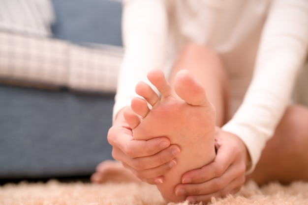 Fußknöchelschmerzfrauen berühren ihren schmerzenden fuß, gesundheitswesen und medizinkonzept