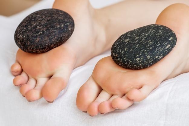 Fußmassage an den beinen der frau durch heiße steine aus nächster nähe.