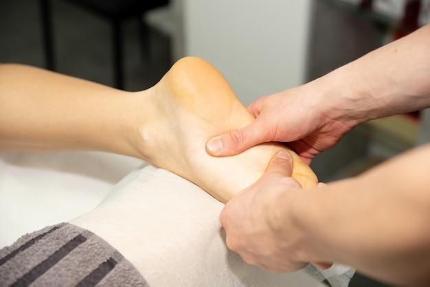 Fußmassage beim patienten. der arzt massiert die füße, fersen und zehen an den beinen