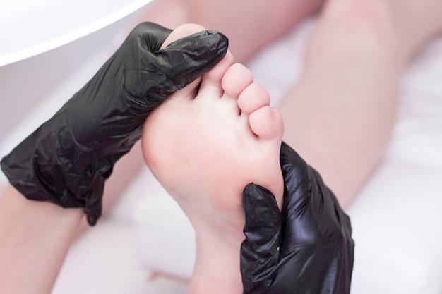 Fußmassage. entspannen. der pediküremeister macht eine fußmassage. masseur.