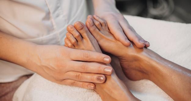 Fußmassageverfahren für kaukasische frau, die im spa-salon liegt