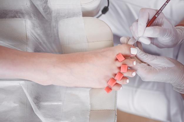 Fußpfleger, der weißen nagellack auf kundenbeinen unter verwendung der schellacklampe tut