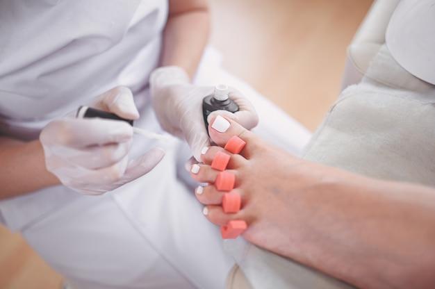 Fußpfleger, der weißen nagellack auf kundenbeinen unter verwendung des zehenfingertrenners tut