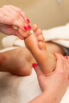 Fußreflexzonenmassage. reflexologe, der in einem wellnesscenter druck auf den großen zeh des kunden ausübt
