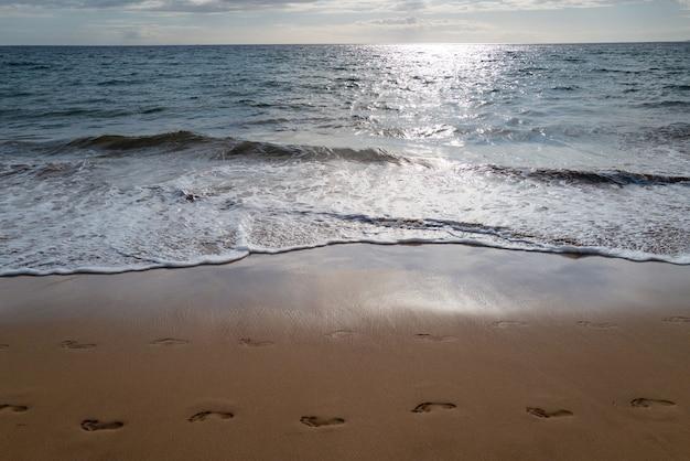 Fußspuren am goldenen sandspuren strand mit goldenem sand türkisfarbenem meerwasser panoramablick auf das meer ...