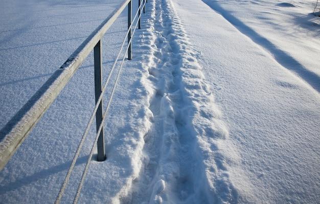 Fußspuren auf schneeverwehungen nach einem spaziergang durch den schnee einer person, die wintersaison in der natur