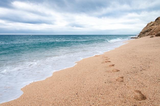 Fußspuren im sand am leeren strand. meereswellen waschen fußspuren im sand