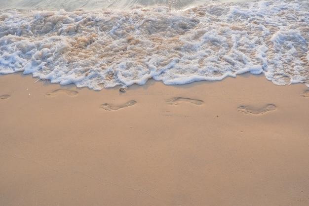 Fußspuren im sand bei sonnenuntergang. schöner tropischer sandstrand mit meereswellen