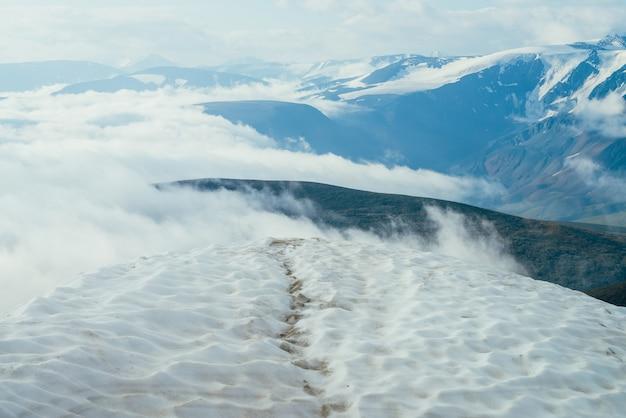 Fußspuren im schnee auf berggipfel über dicken wolken mit blick auf riesige berge und gletscher. schnee auf berggipfel zwischen dicken tiefen wolken. atmosphärische alpenlandschaft. wunderbare hochlandlandschaft.