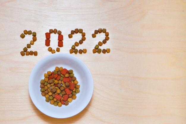 Futter für katzen und hunde und das neue jahr. etikett für trockenfutter. leckerbissen für haustiere im jahr 2022