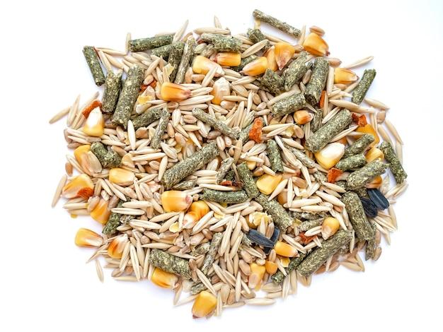 Futter für nagetiere aus hafer, graspellets, tierfutter, mais, weizen isoliert auf weißem hintergrund.