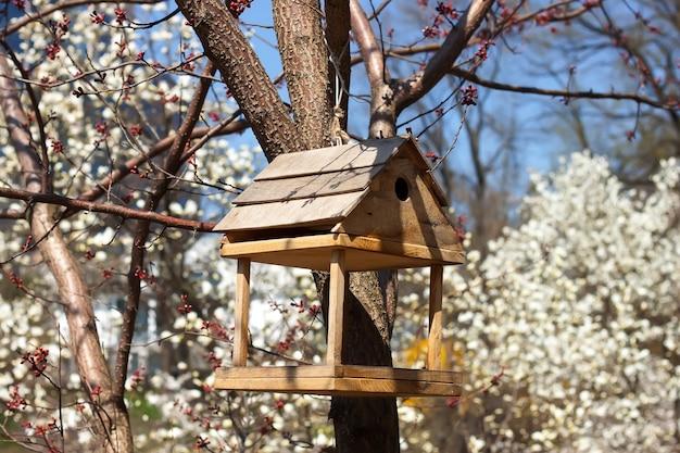Futterautomat für vögel im blühenden frühlingsgarten