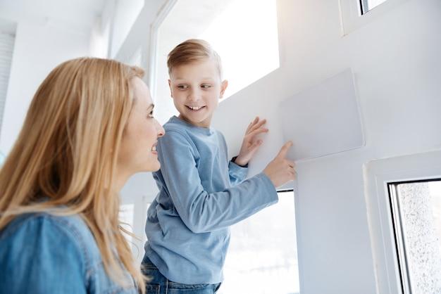 Futuristische entwicklung. netter glücklicher intelligenter junge, der den sensorischen knopf auf dem bedienfeld drückt und lächelt, während er lernt, wie man es benutzt